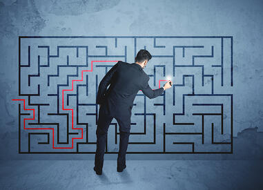 Man in a suit completing a complex puzzle
