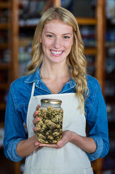 Budtender holding cannabis for a customer