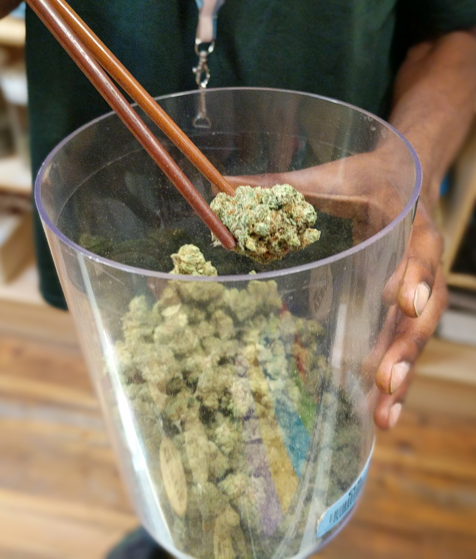 Budtender showing product in a cannabis dispensary