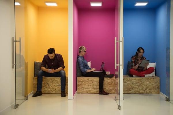 Flexible workspace members working in phone booths