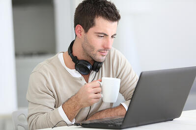 Coworking space member enjoying coffee while working