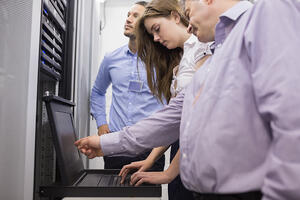 Employees reviewing data in a server room