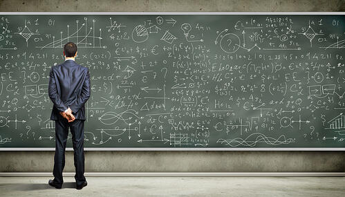 Man in a suit reviewing complex calculations