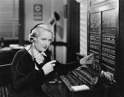 Woman operating a manual telephone switchboard