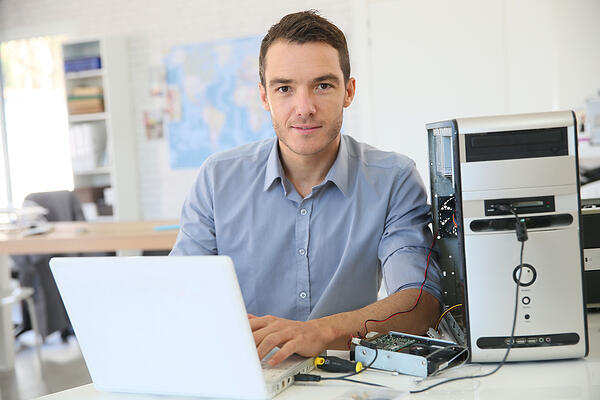 Facilities manager fixing a desktop computer