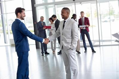 Two business people greeting each other with a handshake in modern reception area