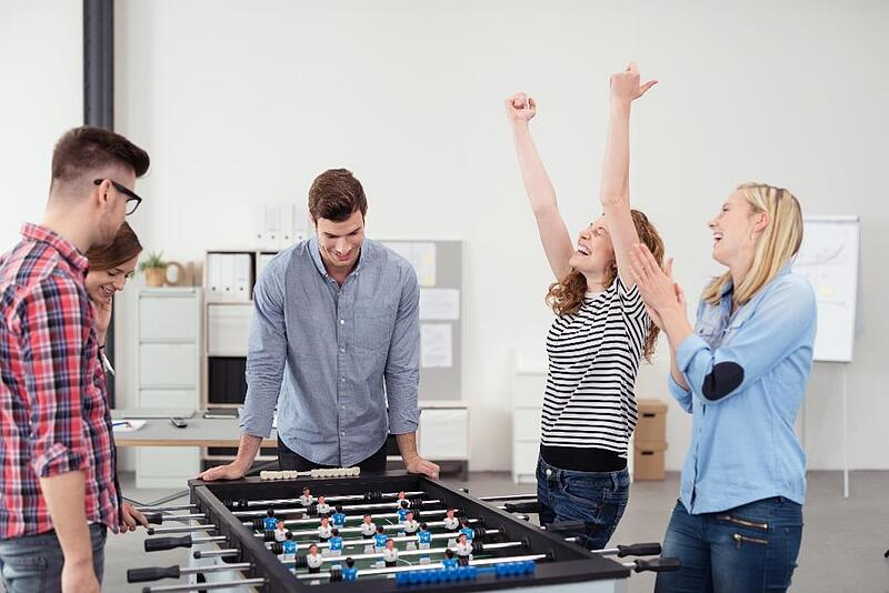 Employees playing foosball together