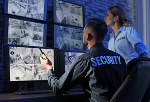 Employees reviewing visitor management security data
