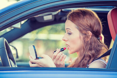 Woman applying makeup while driving a car