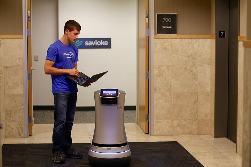 Man working with an office automation robot in an elevator bank