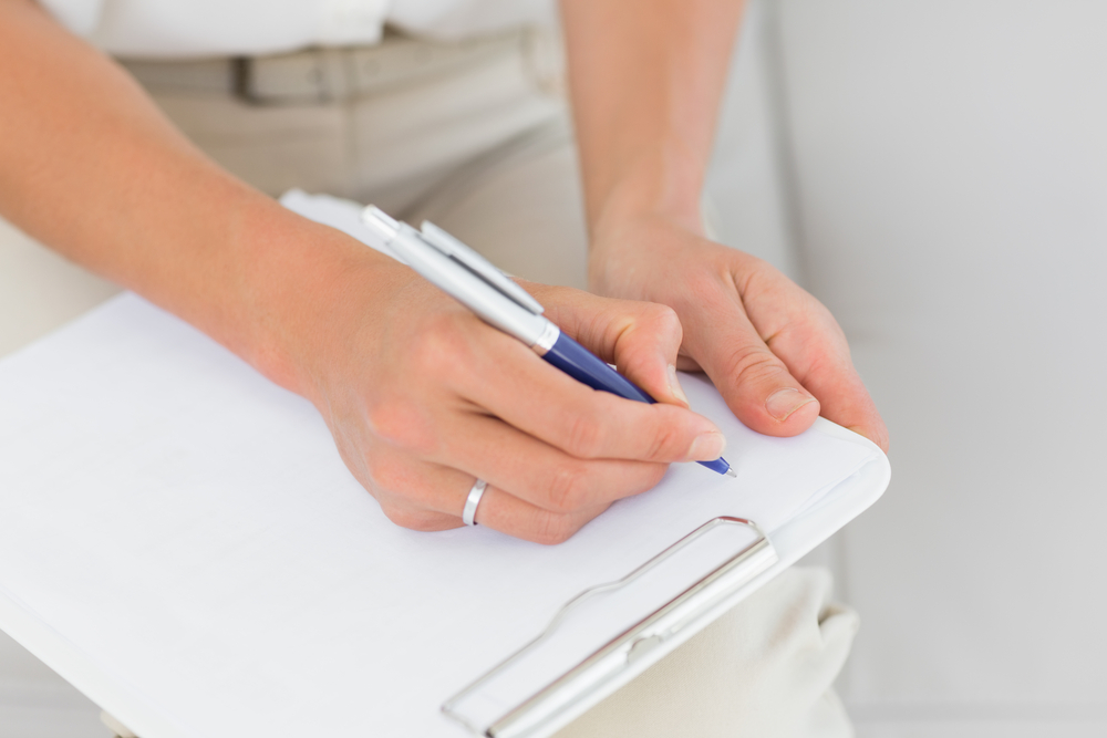 Signing into a paper visitor logbook