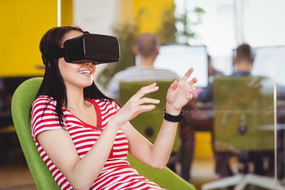 Happy young female executive enjoying augmented reality glasses at creative office
